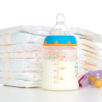 stack of diapers nipple soother and baby feeding bottle with mil
